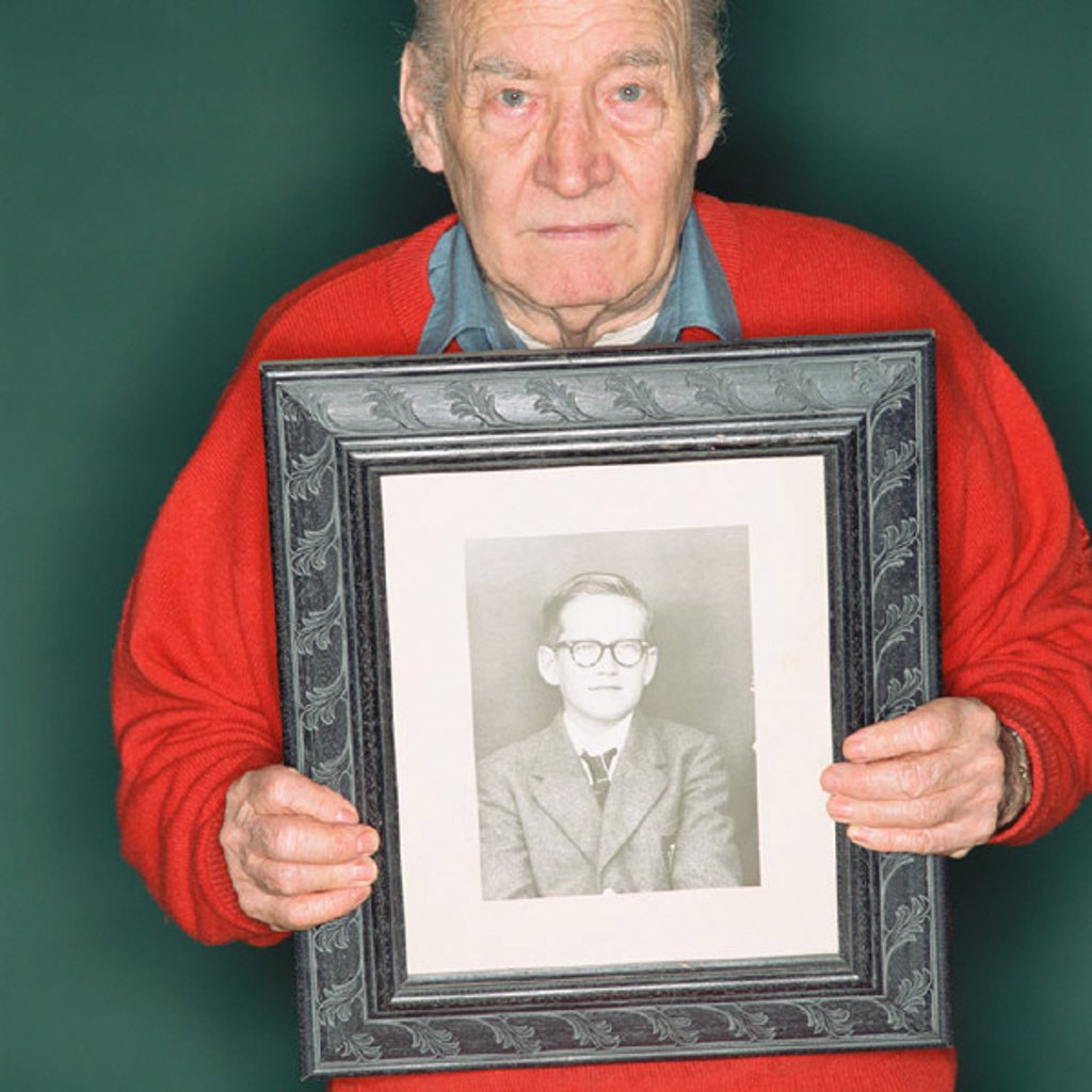 Stock Photo: 1439R-1124380 Senior man holding a portrait of a young man