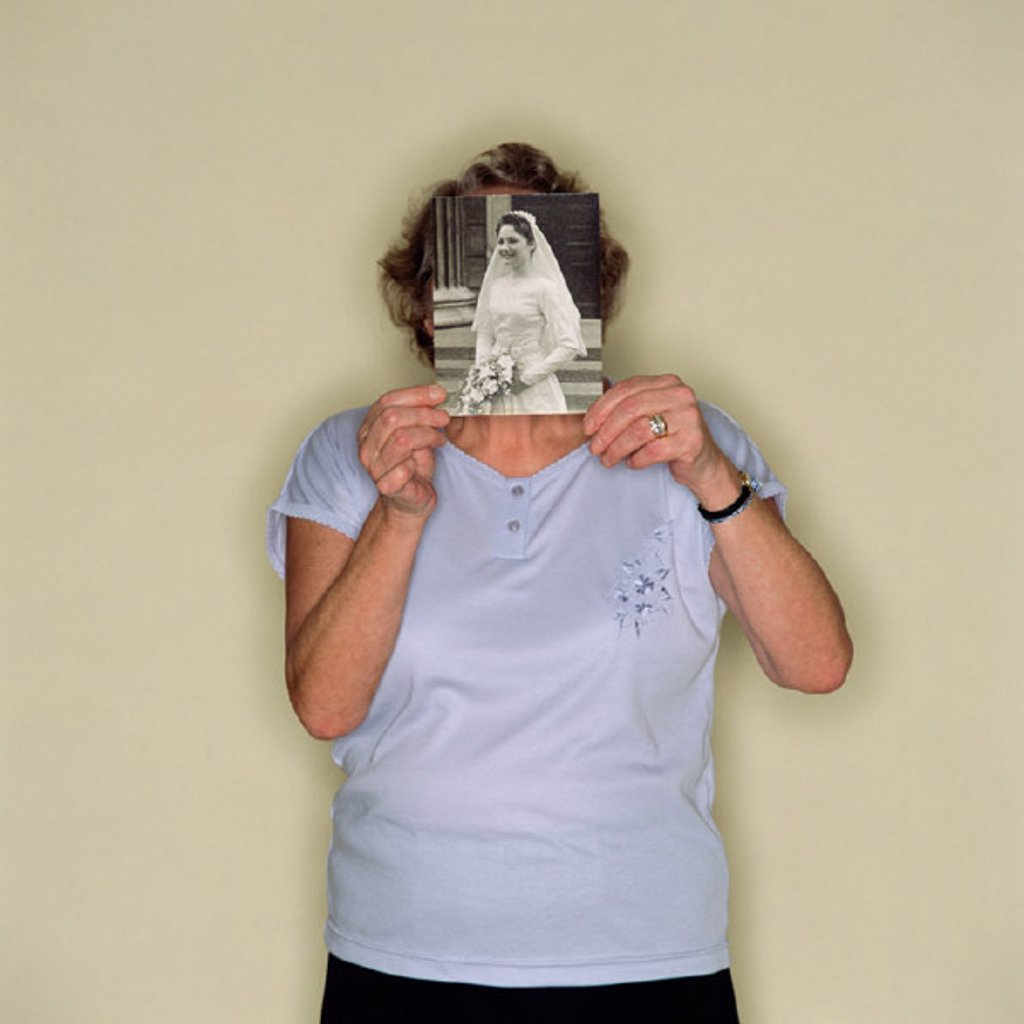 Senior woman holding a photo of a bride : Stock Photo