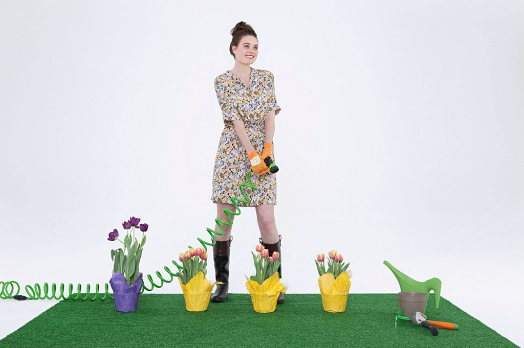 Woman with hose and flowers on artificial turf : Stock Photo