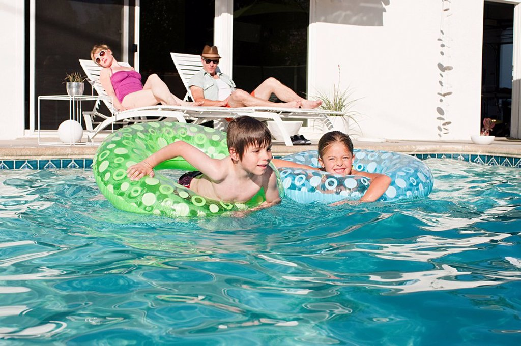 Family and outdoor swimming pool : Stock Photo