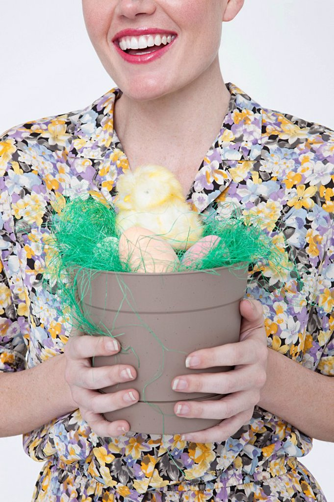 Young woman with easter chick and eggs in flower pot : Stock Photo