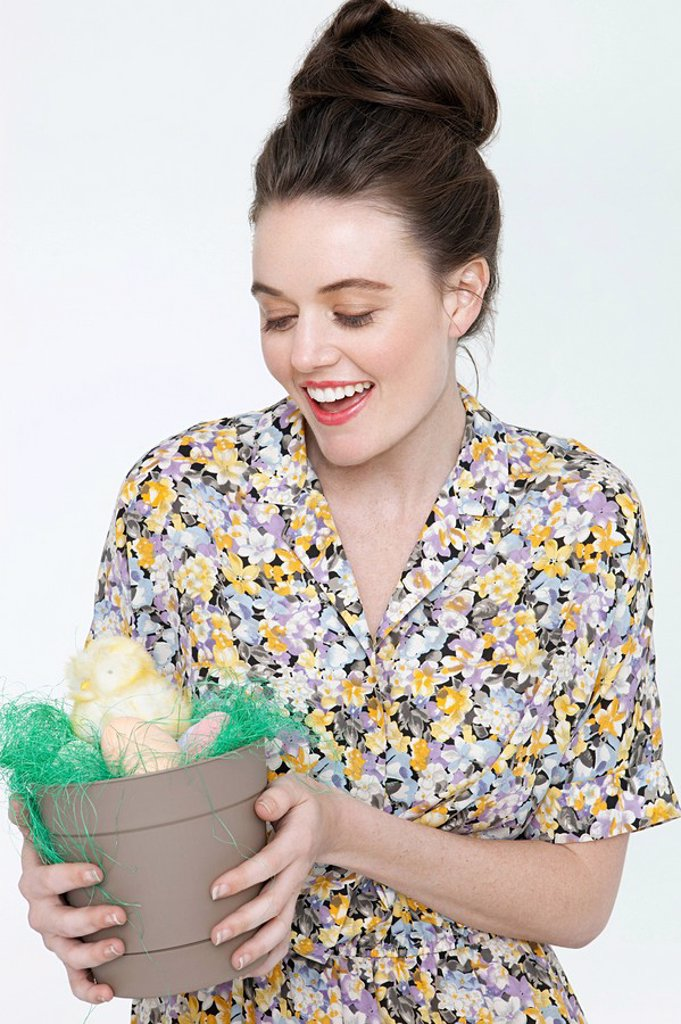 Stock Photo: 1439R-1125055 Young woman with easter chick and eggs in flower pot