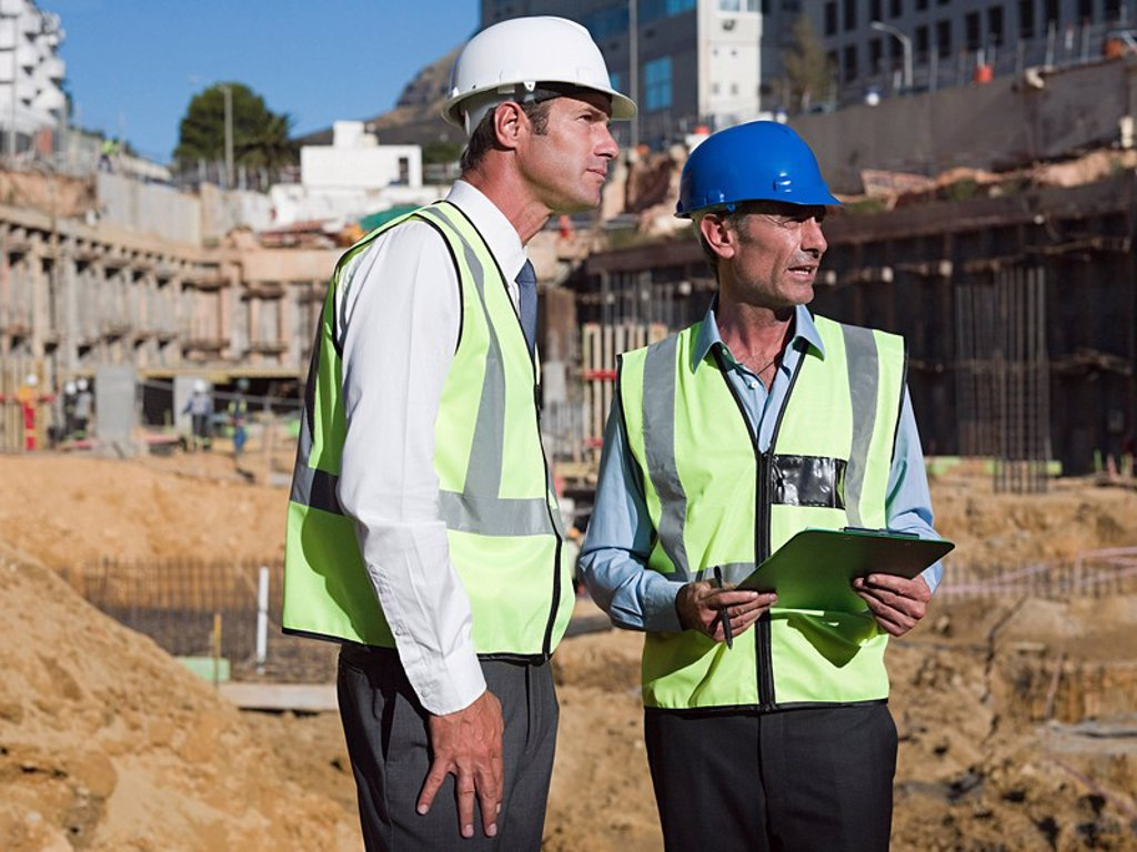 Mature men meeting on construction site : Stock Photo