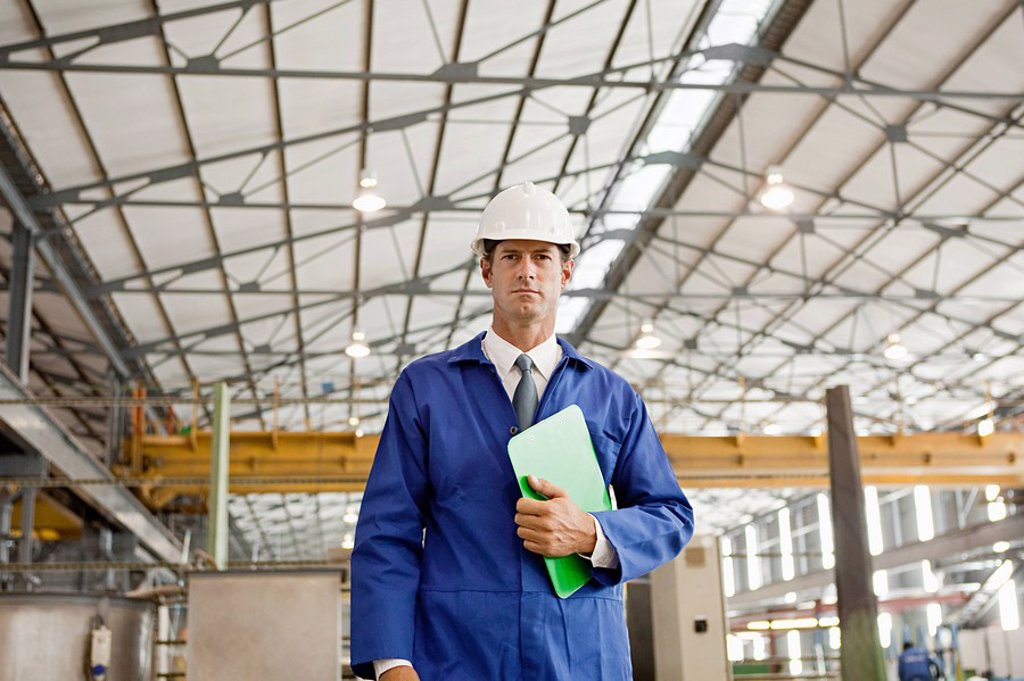 Stock Photo: 1439R-1125564 Mature man with clipboard in factory