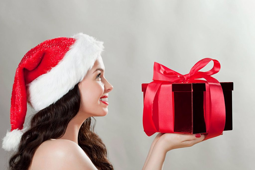 Young brunette woman wearing Santa hat with Christmas present : Stock Photo