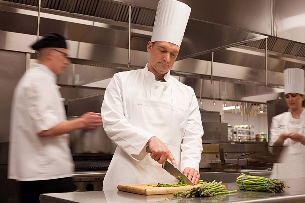 Stock Photo: 1439R-1125851 Chefs preparing food in commercial kitchen