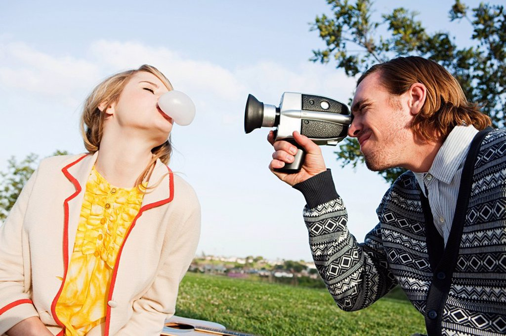 Man filming girlfriend blowing bubble gum : Stock Photo