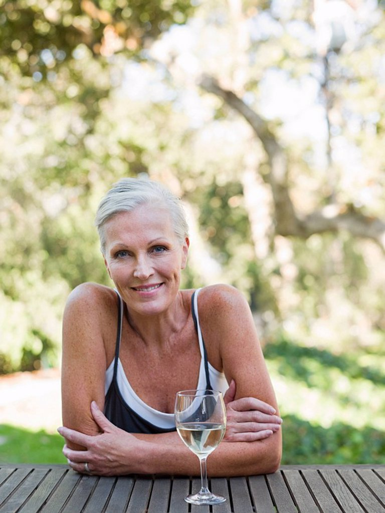 Stock Photo: 1439R-1126461 Mature woman outdoors with wine