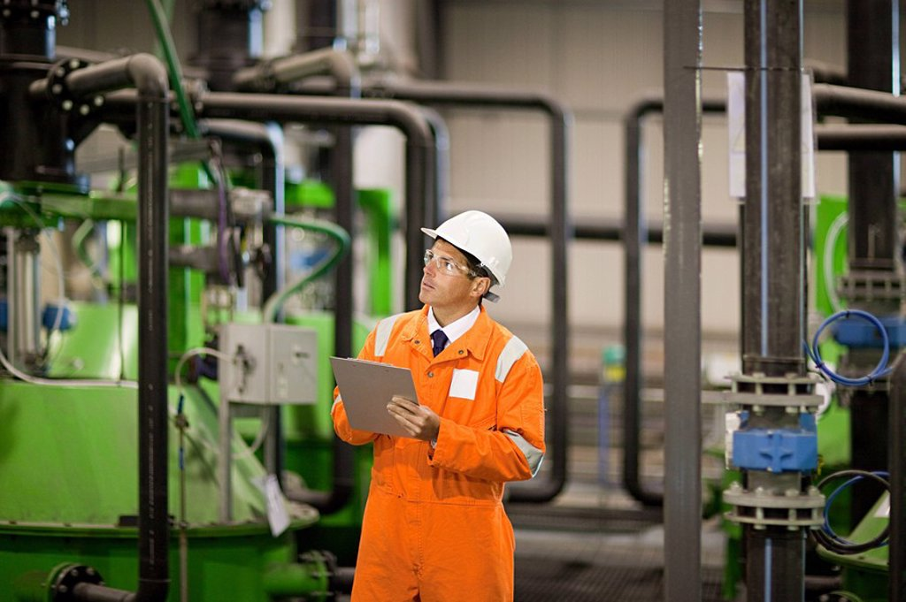Stock Photo: 1439R-1126529 Engineer inspecting machinery in factory
