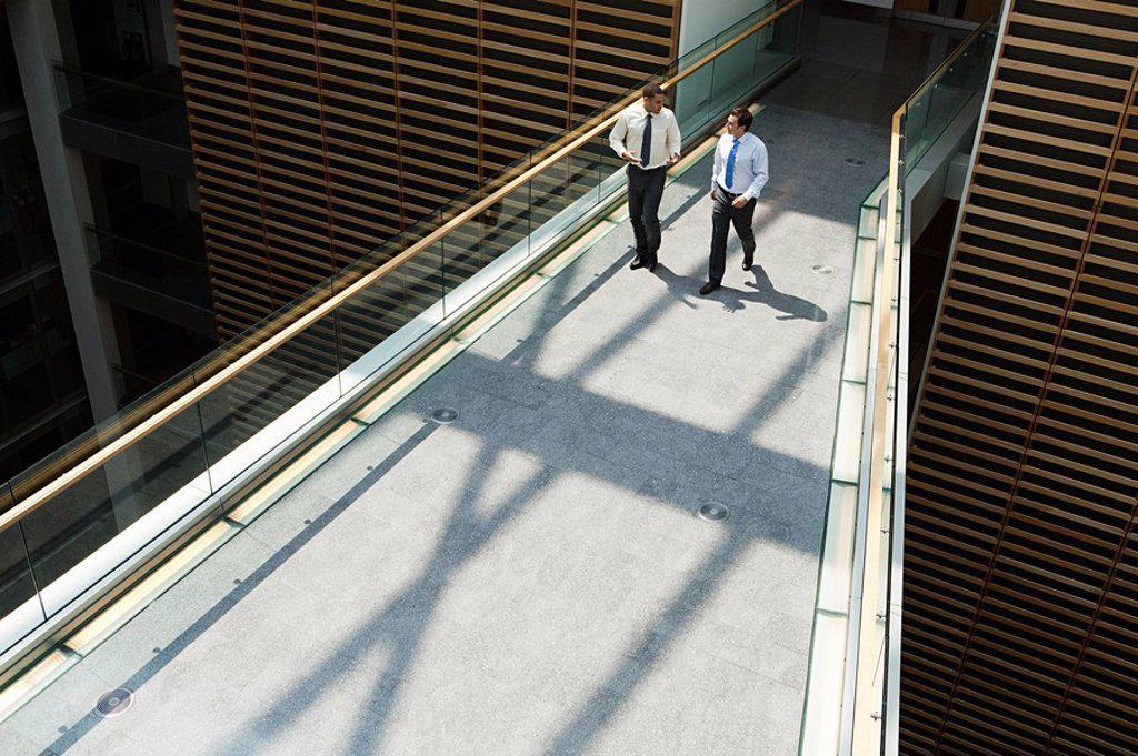 Stock Photo: 1439R-1127295 Businessmen on office walkway