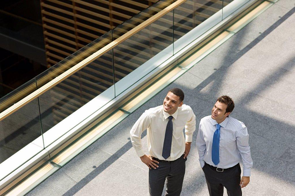 Stock Photo: 1439R-1127302 Businessmen on office walkway