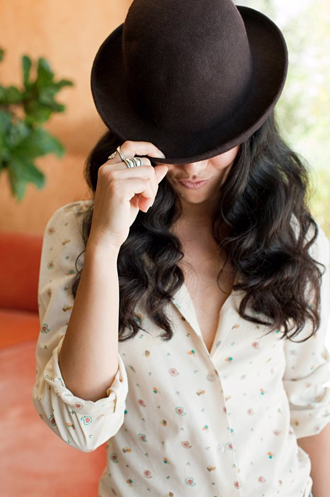 Young woman with brown hair wearing bowler hat : Stock Photo