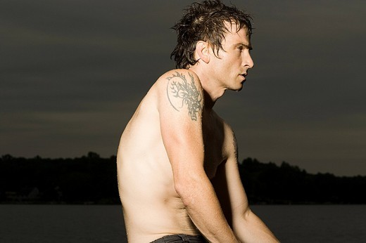 Stock Photo: 1439R-1127851 Male swimmer with tattoo on shoulder