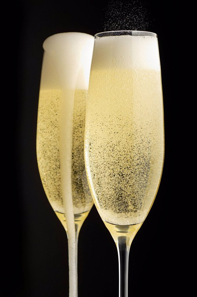 Two full champagne glasses with champagne overflowing : Stock Photo