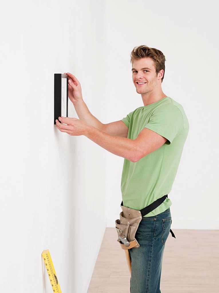 Young man hanging picture on wall : Stock Photo