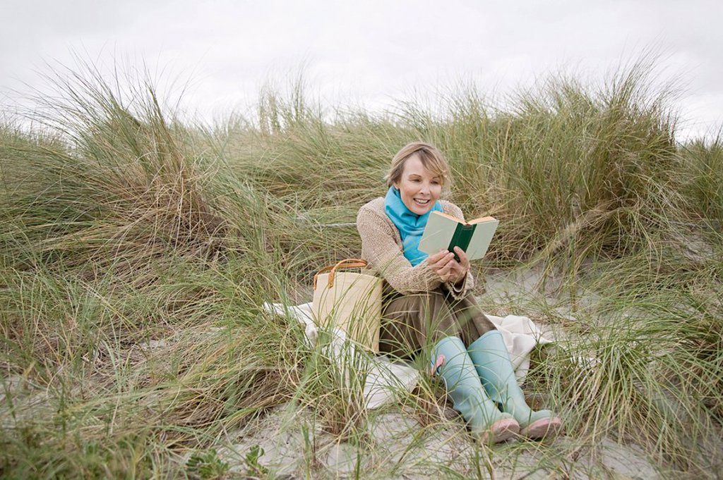 Woman reading a book on a dune : Stock Photo