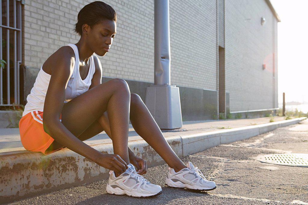 Runner sitting on sidewalk : Stock Photo