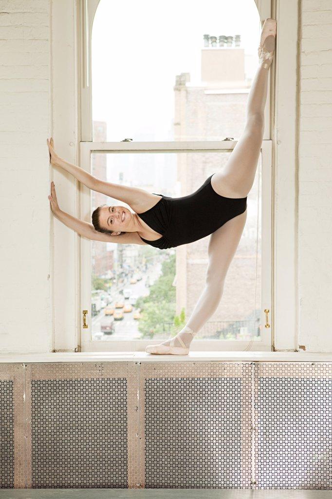 Ballerina stretching in window : Stock Photo