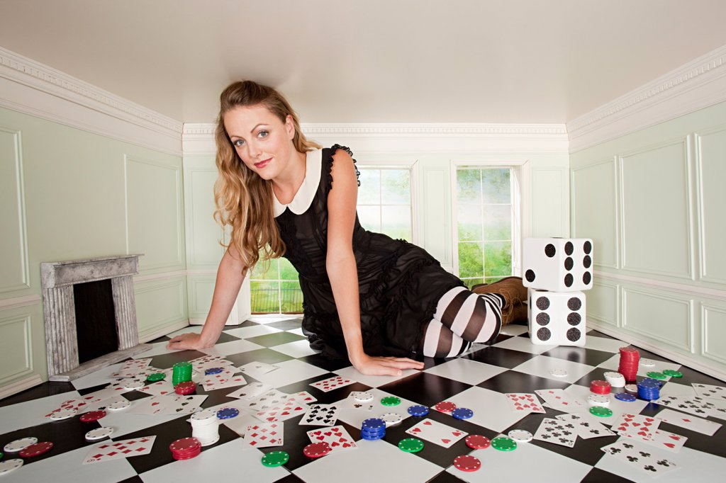 Stock Photo: 1439R-1130419 Young woman in small room with playing cards and dice