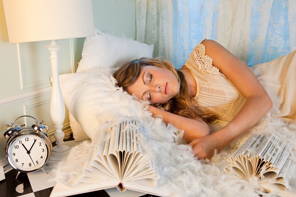 Young woman sleeping amongst pillow feathers : Stock Photo