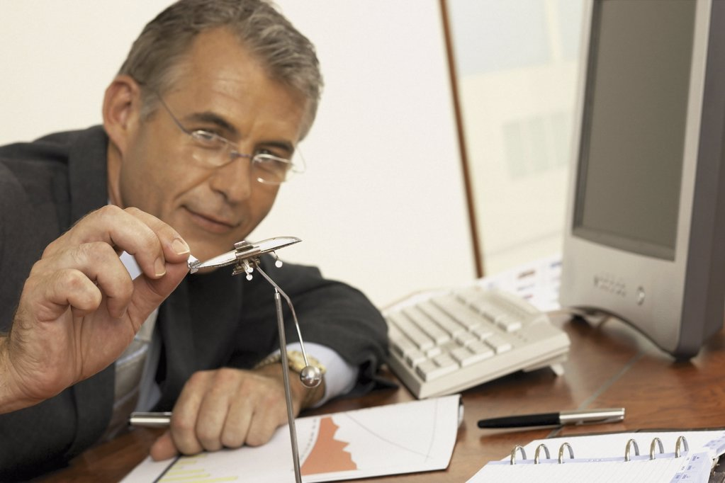 Stock Photo: 1439R-113064 Businessman playing with executive toy