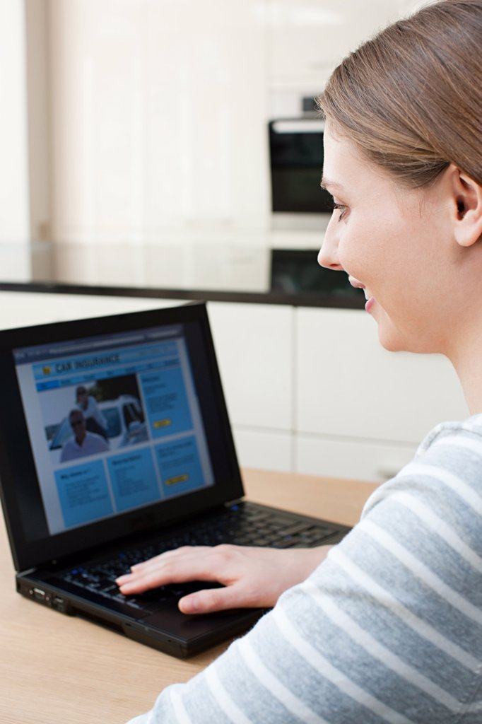 Young woman looking at car insurance on laptop : Stock Photo
