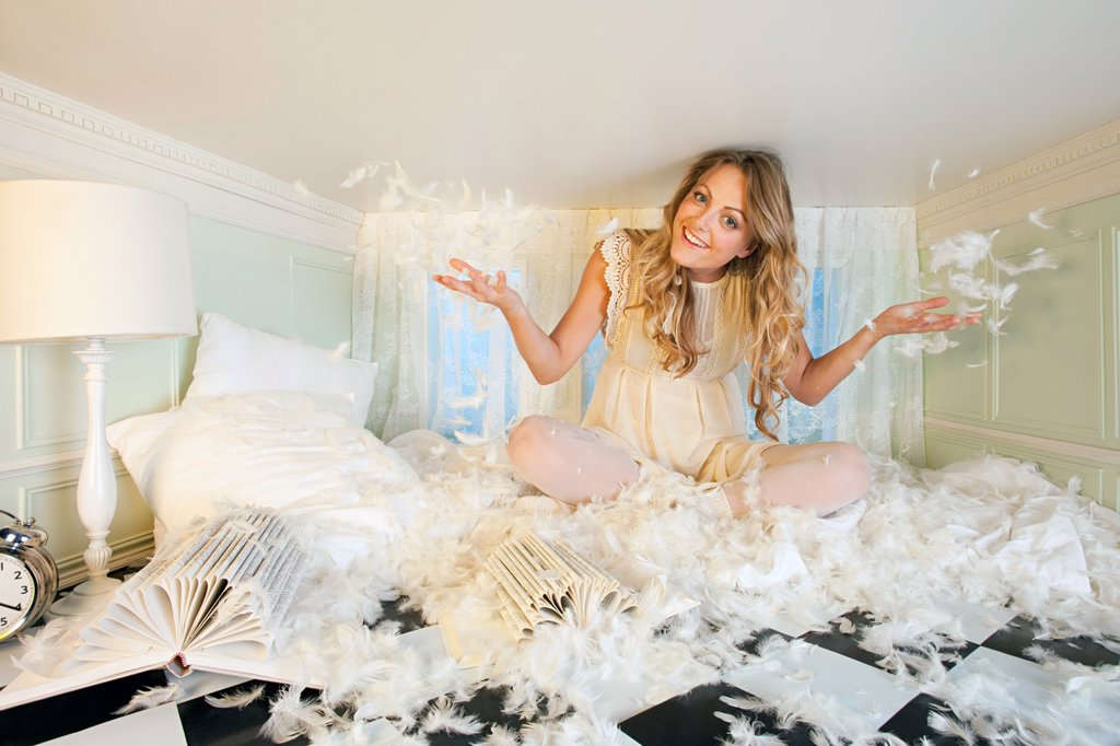 Stock Photo: 1439R-1130831 Young woman in small room, throwing pillow feathers