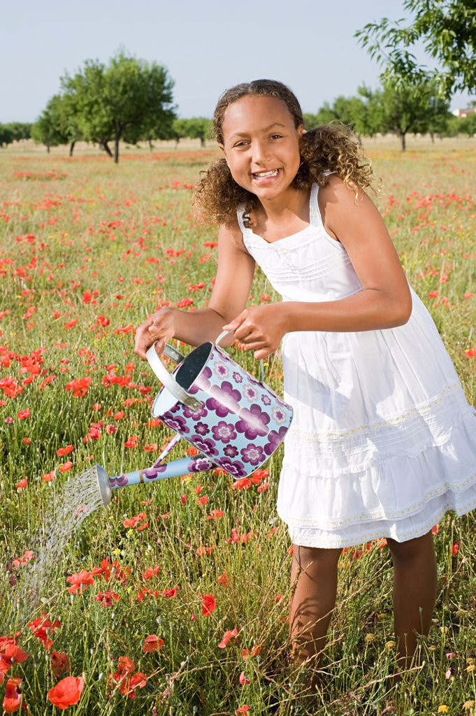 Young girl watering poppy field with watering can : Stock Photo