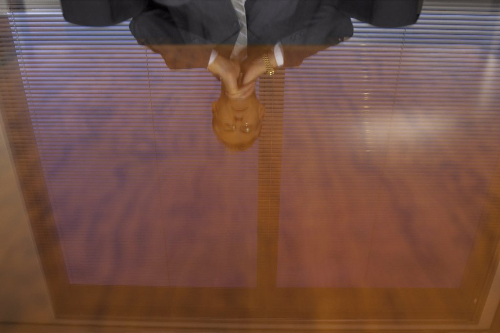 Stock Photo: 1439R-113084 Businessman reflected in glass table