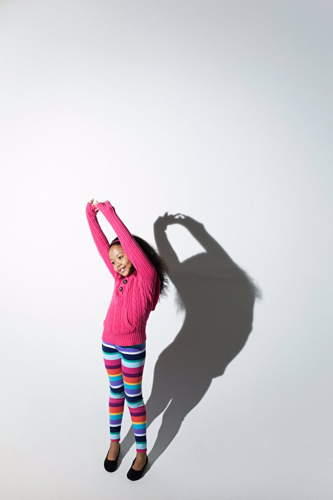 Stock Photo: 1439R-1130917 Girl with arms raised and shadow