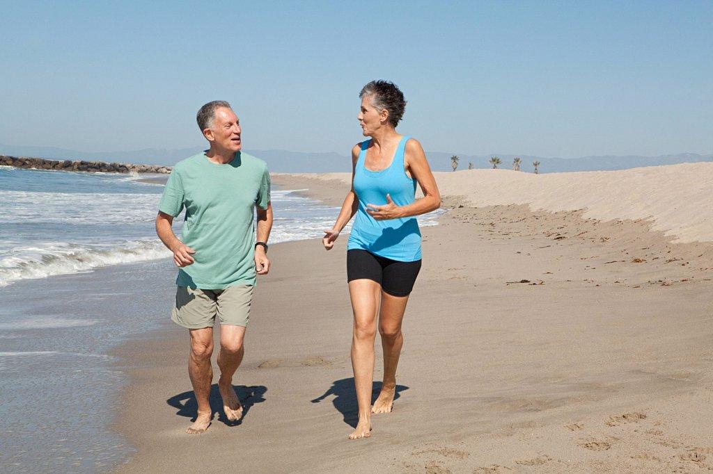 Senior couple jogging on beach : Stock Photo