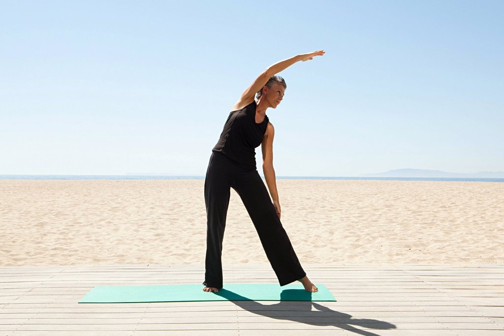 Senior woman doing yoga on beach : Stock Photo