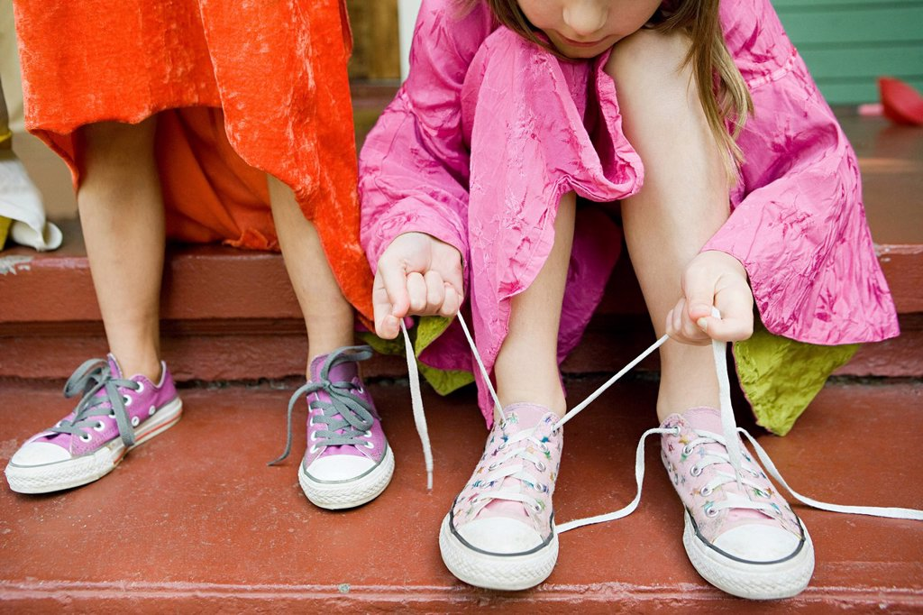 Two girls, one tying up shoelace : Stock Photo