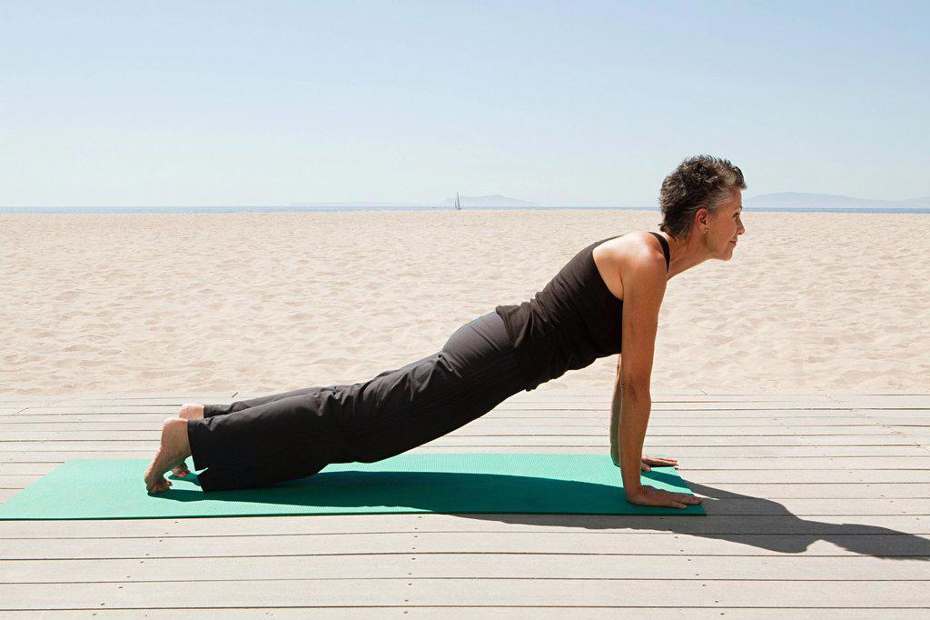 Stock Photo: 1439R-1131716 Senior woman doing yoga on beach