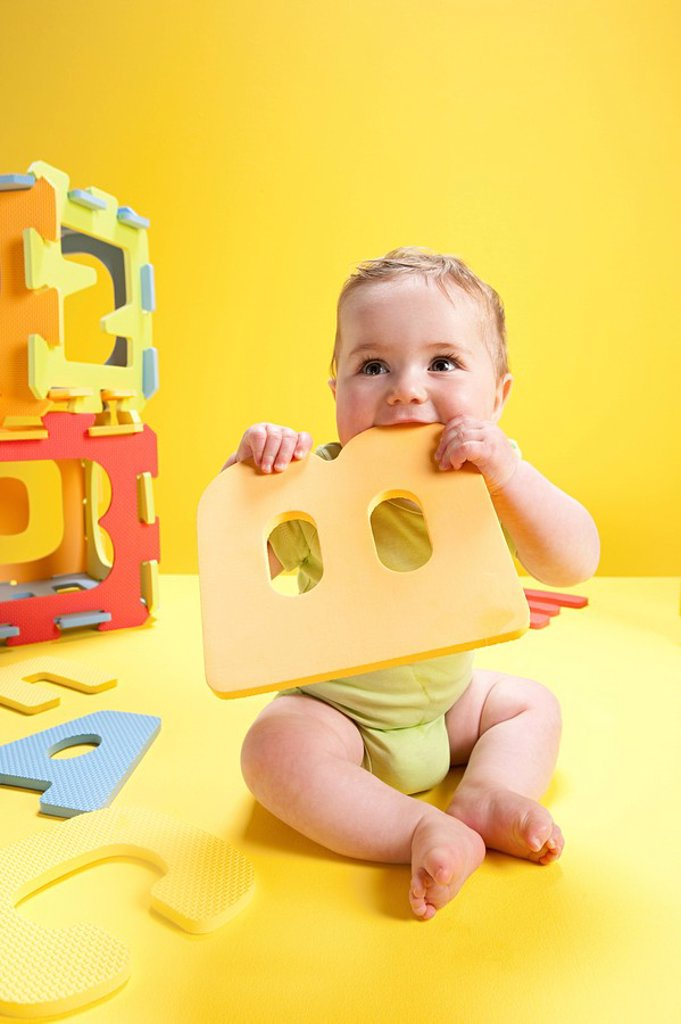 Stock Photo: 1439R-1132180 Baby boy playing with toy alphabet letters