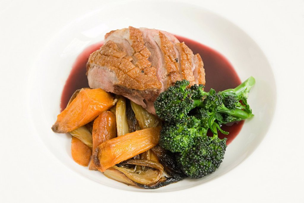 Roast duck with vegetables and jus : Stock Photo
