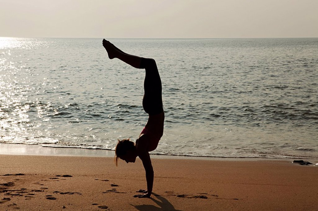 Woman practicing yoga on a beach at sunset : Stock Photo