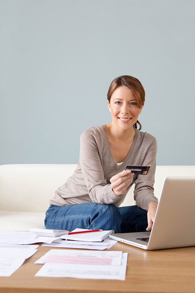 Young woman with credit card using laptop : Stock Photo