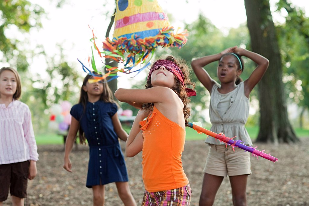 Stock Photo: 1439R-1133579 Girl at birthday party hitting pinata