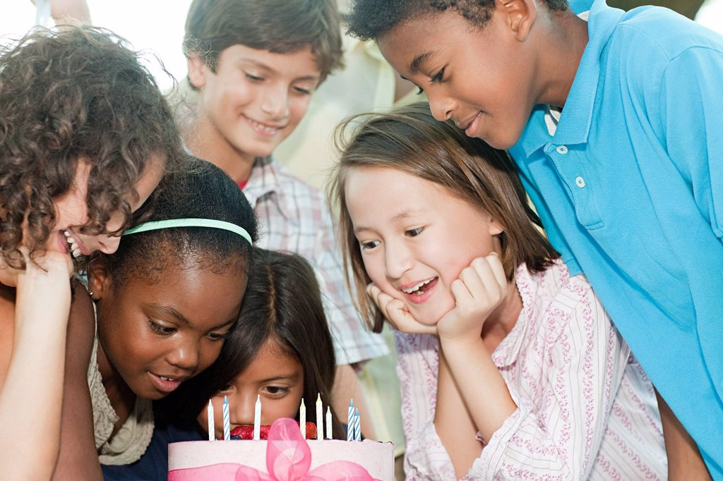 Stock Photo: 1439R-1133585 Children at birthday party with birthday cake