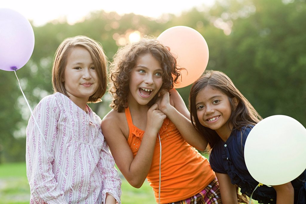 Girls at birthday party holding balloons : Stock Photo