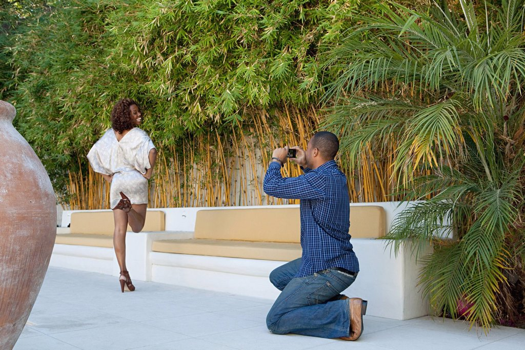 Man taking a picture of girlfriend as she poses for camera : Stock Photo