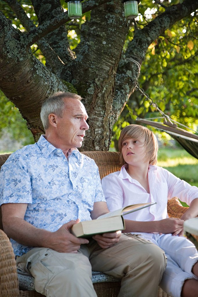 Stock Photo: 1439R-1133786 Father and son with book, in conversation