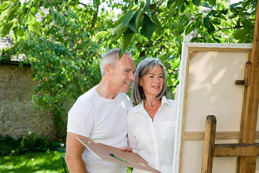 Mature couple, woman painting at easel : Stock Photo