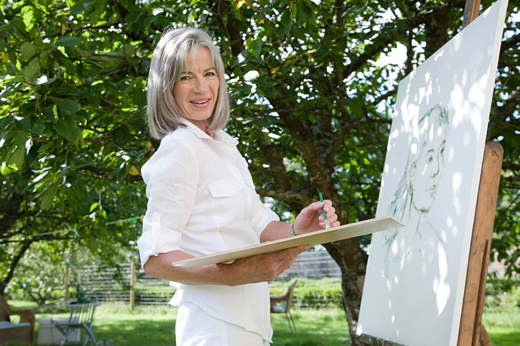Mature woman painting at easel : Stock Photo