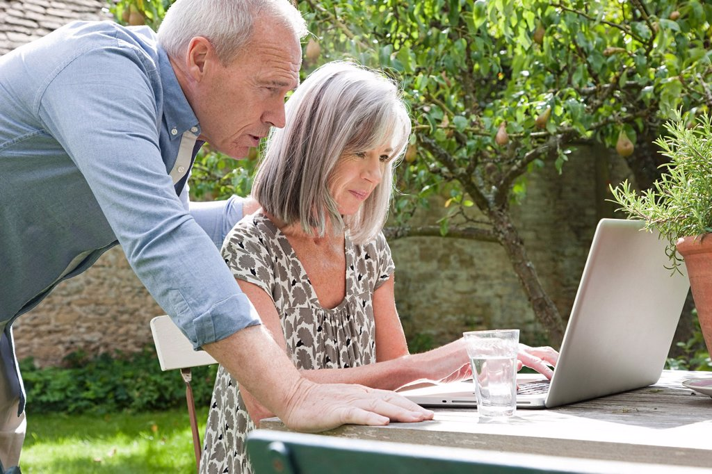 Mature couple using laptop : Stock Photo