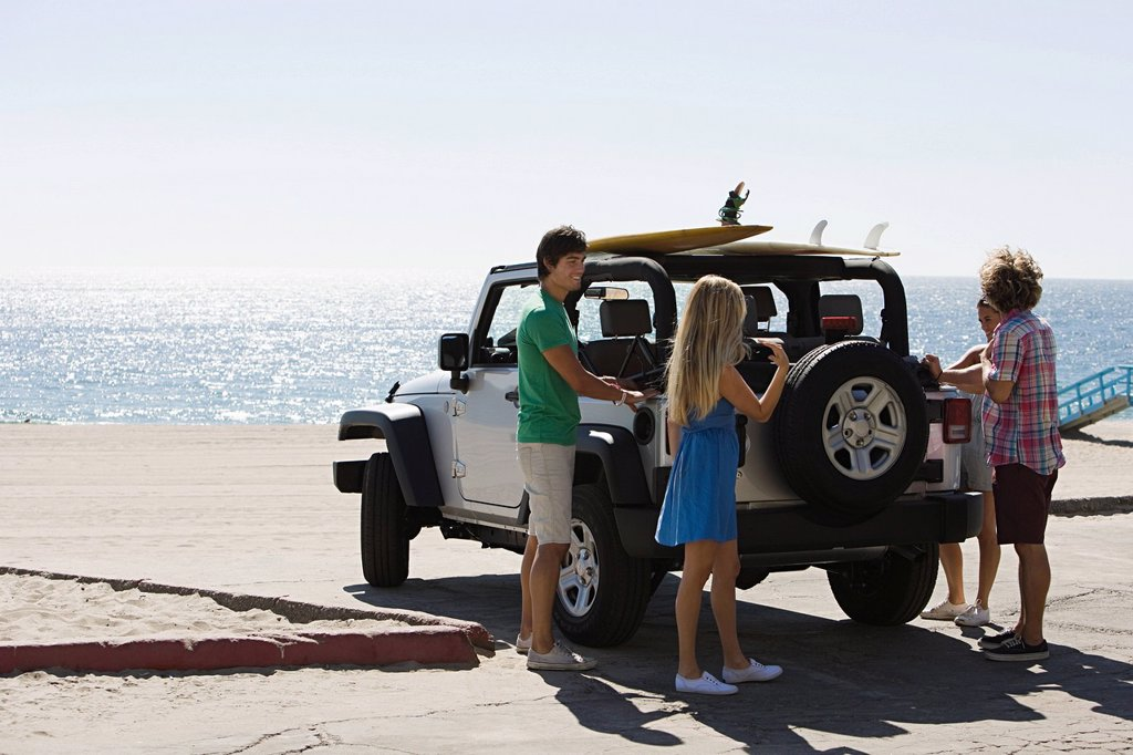 Stock Photo: 1439R-1133985 Friends by SUV at the coast