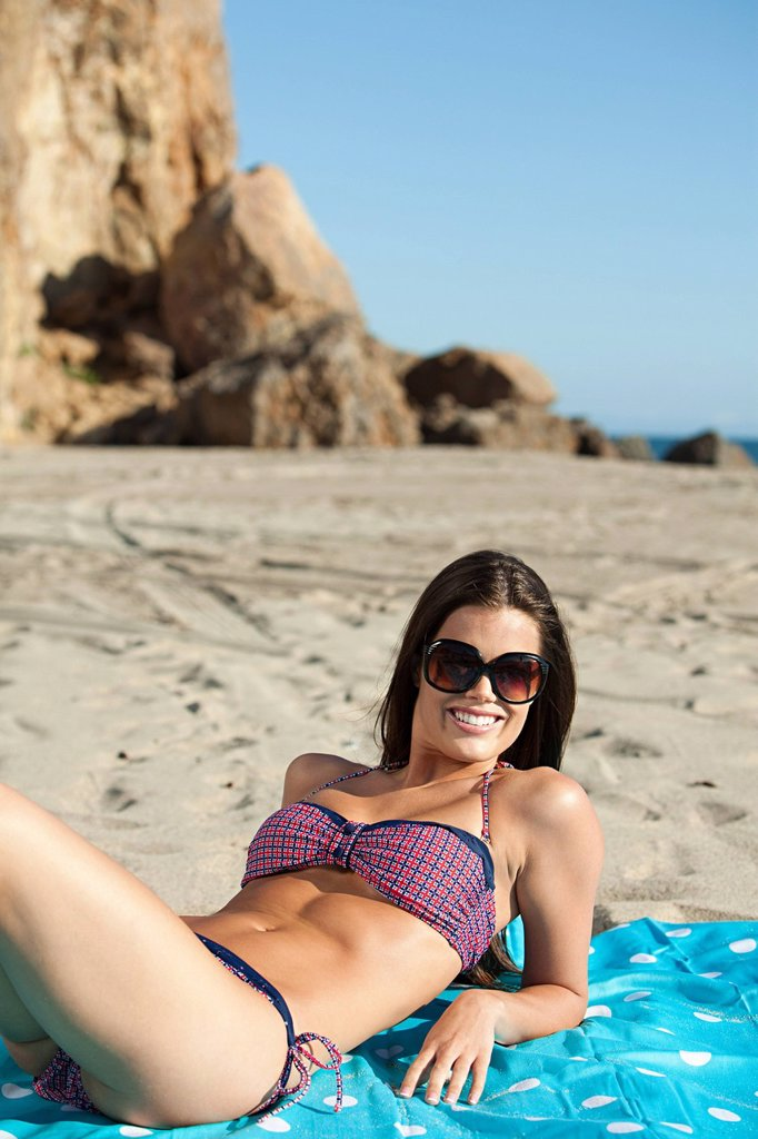 Young woman sunbathing at the beach : Stock Photo