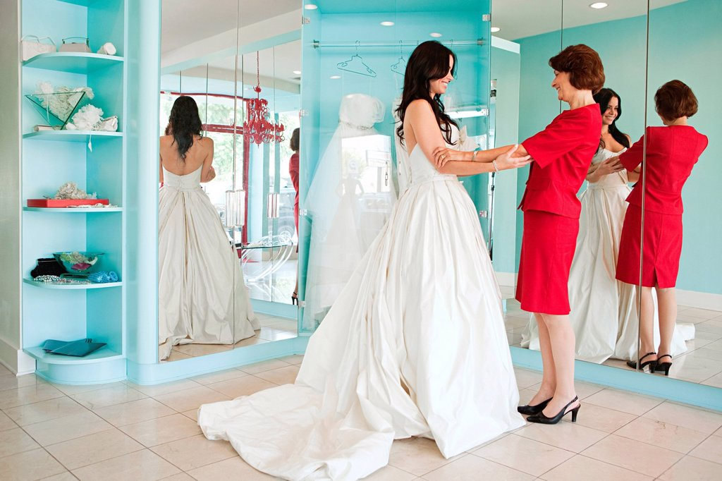 Daughter trying on wedding dress, holding hands : Stock Photo