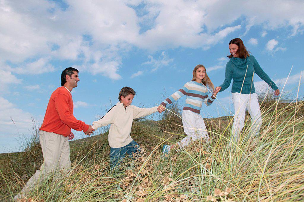 Stock Photo: 1439R-1134542 Family walking hand in hand over dune